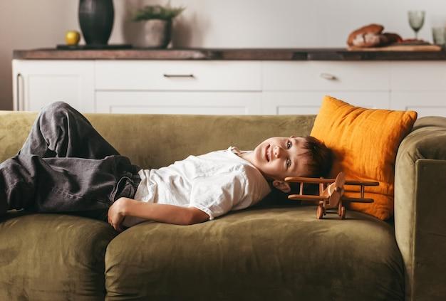 Chłopiec leży na kanapie z samolocikiem i snami. obraz koncepcja domu czasu dla dzieci.