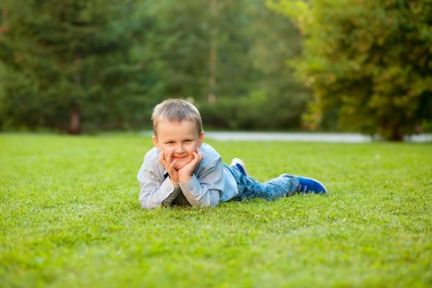 Chłopiec leży na trawie z miejsca na kopię