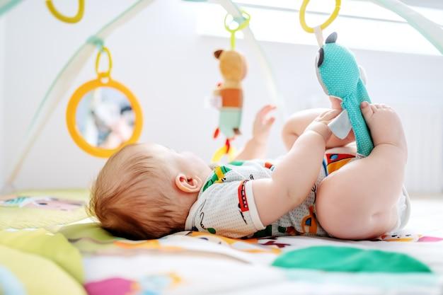 Chłopiec leży w łóżku i bawi się zabawkami szopka.