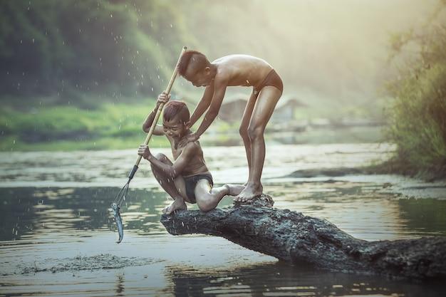 Chłopiec łowi przy rzeką