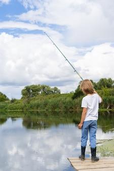 Chłopiec łowi ryby na drewnianym moście w pobliżu stawu