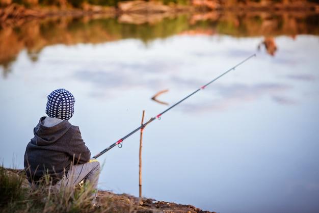 Chłopiec łowi ryby w rzece.