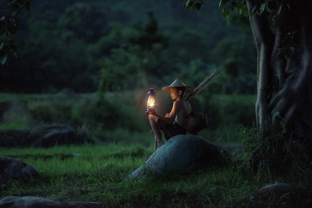 Chłopiec łowi z lampionem