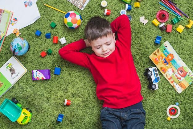 Chłopiec lying on the beach na zielonym dywanie