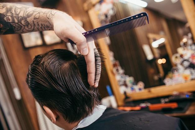 Chłopiec ma jej włosy ciie w modnisia fryzjera męskiego sklepie