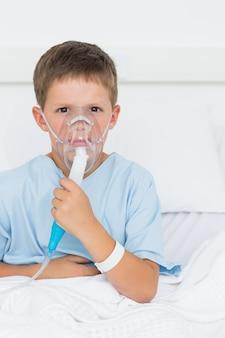 Chłopiec ma na sobie maskę tlenową w oddziale szpitala