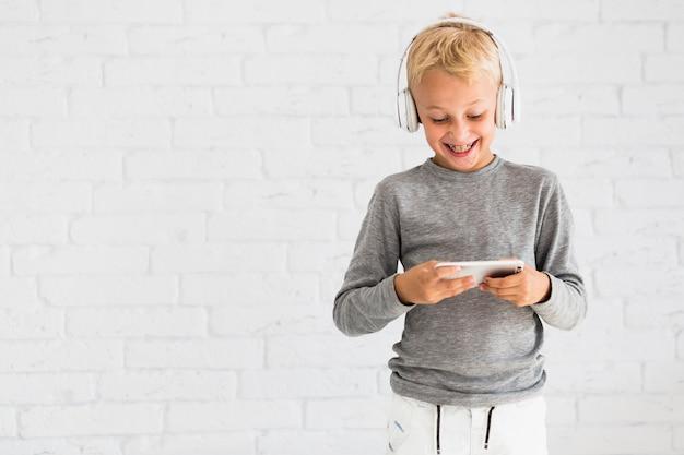 Chłopiec ma zabawę z smartphone i słuchawkami