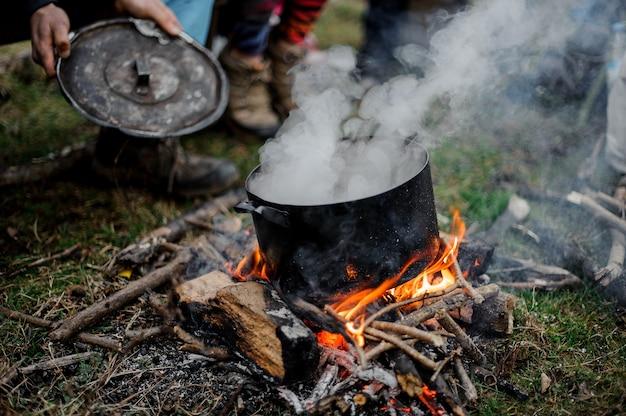 Chłopiec macha ciosem z osłoną na patelnię na ognisku nad zieloną trawą w lesie