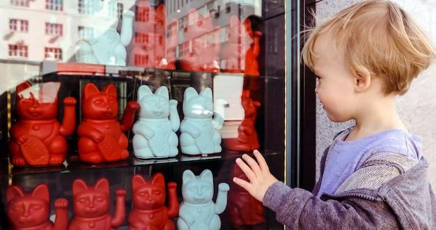 Chłopiec macha ręką podczas oglądania maneki neko