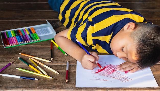 Chłopiec malowanie na białym papierze w kolorze drewna