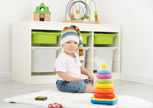 Chłopiec maluch dziecko bawi się piramidą w domu. tworzenie gier dla dzieci.