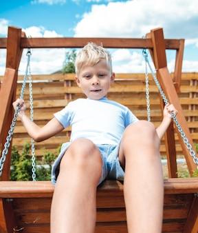Chłopiec maluch dziecko huśtawka na placu zabaw na podwórku w lecie