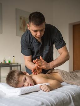 Chłopiec maluch relaksuje się po masażu leczniczym. fizjoterapeuta pracujący z pacjentem w klinice z tyłu dziecka