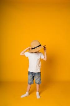 Chłopiec maluch stoi bokiem w słomkowym kapeluszu na żółtej powierzchni z miejscem na tekst