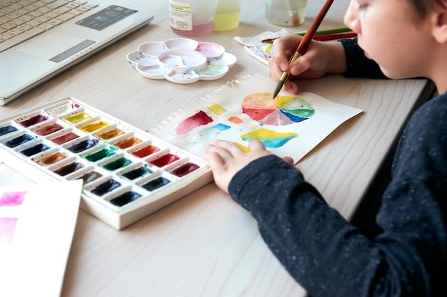 Chłopiec maluje obrazki farbami akwarelowymi podczas lekcji sztuki online