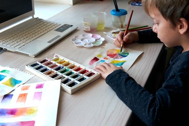 Chłopiec maluje obrazy farbami akwarelowymi podczas lekcji plastyki