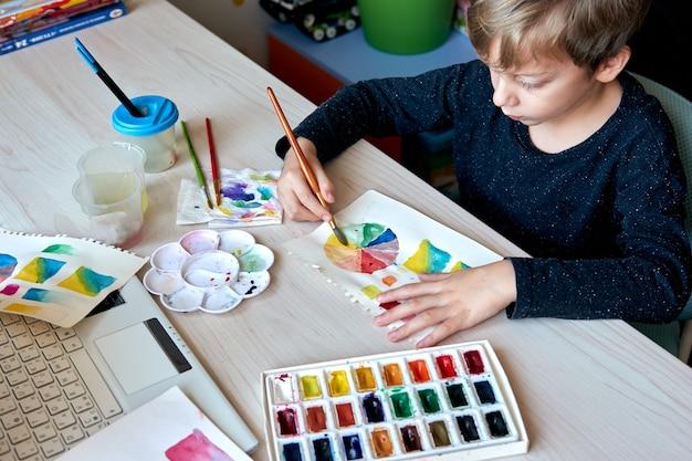 Chłopiec maluje obrazy farbami akwarelowymi podczas lekcji sztuki. uczeń na rysowaniu pędzlem. koło kolorów akwareli i paleta. lekcje hobby dla początkujących z teorii kolorów