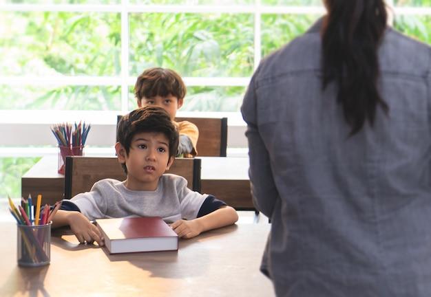 Chłopiec martwi się i nastawiony na temat nauczyciela w klasie