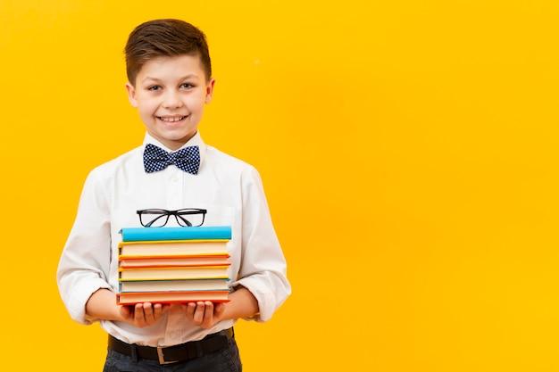 Chłopiec miejsca kopiowania stosu książek