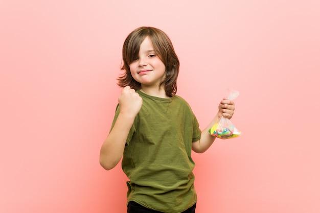 Chłopiec mienia caucasian caucasian cukierki pokazuje pięść kamera, agresywny wyraz twarzy.