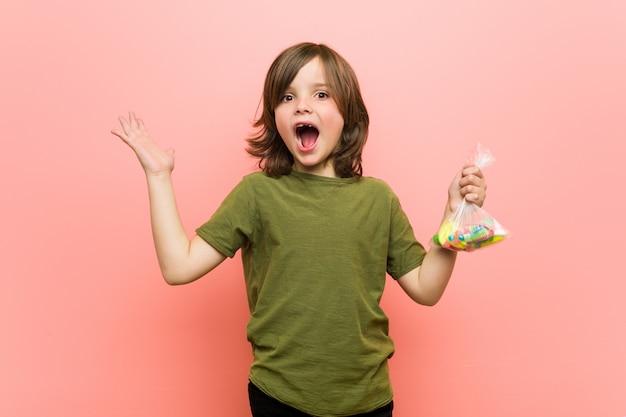 Chłopiec mienia caucasian caucasian cukierki świętuje zwycięstwo lub sukces
