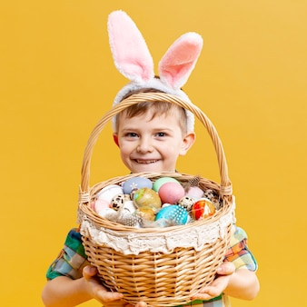 Chłopiec mienia kosz z malującymi jajkami