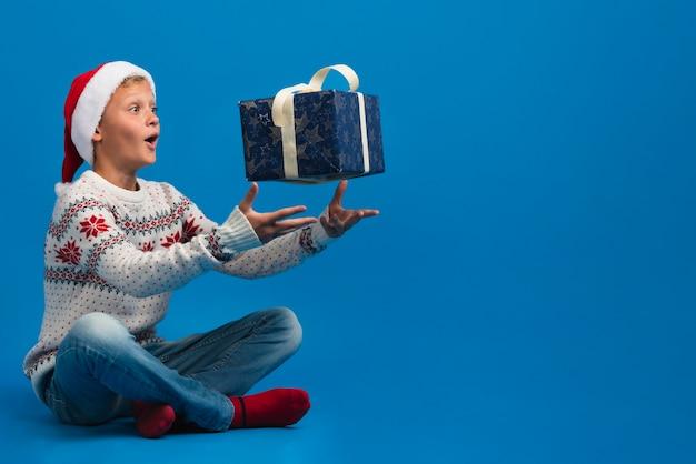 Chłopiec miotania prezenta kopii przestrzeń