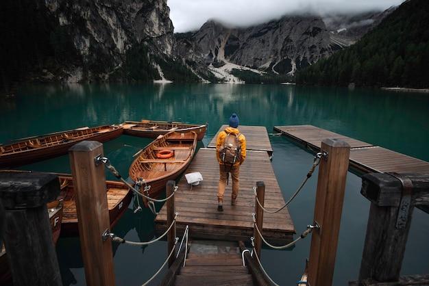 Chłopiec młodego podróżnika z niebieskim kapeluszem, plecakiem vintage i żółtym płaszczem przeciwdeszczowym na molo w lago di braies otoczonym górami włoskich alp