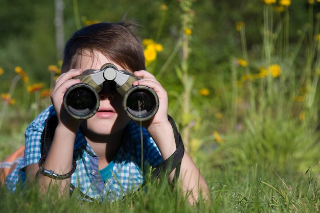 Chłopiec młody badacz bada z lornetki środowiskiem w letnim ogródzie
