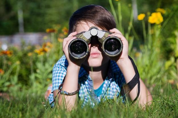 Chłopiec młody badacz bada z lornetki środowiskiem w zieleń ogródzie