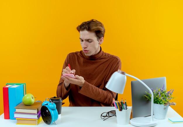 Chłopiec młody student siedzi przy biurku z narzędzi szkolnych pisze coś na białym tle na żółtej ścianie