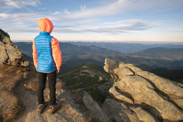 Chłopiec młody turysta stojący w górach z widokiem na górski krajobraz