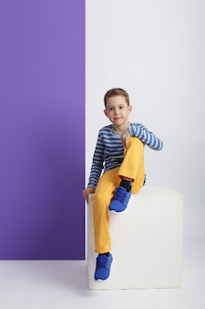 Chłopiec moda w stylowe ubrania na tle kolorowe ściany. jesienne jasne ubrania dla dzieci, dziecko pozuje na kolorowym fioletowym różowym tle. rosja, swierdłowsk, 6 kwietnia 2019 r.