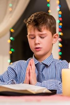 Chłopiec modli się przy stole. dziecko modli się w nocy. świąteczna modlitwa w kościele miejskim. młodzieńczy parafianin na boże narodzenie.