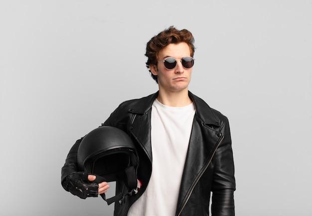 Chłopiec motocyklista czuje się smutny, zdenerwowany lub zły i patrzy w bok z negatywnym nastawieniem, marszcząc brwi w niezgodzie