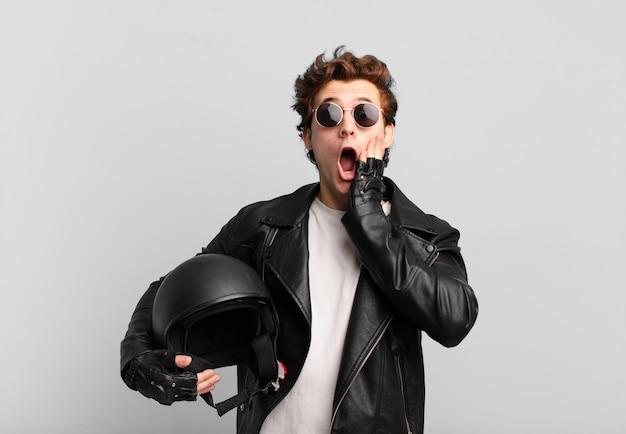 Chłopiec motocyklista jest zszokowany i przestraszony, wygląda na przerażonego z otwartymi ustami i dłońmi na policzkach