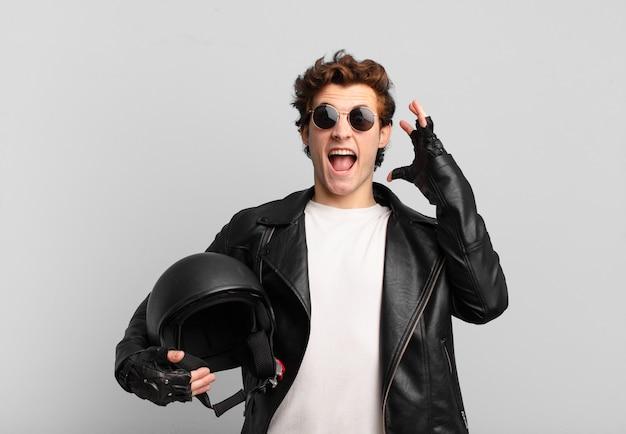 Chłopiec motocyklista krzyczy z rękami w górze, czuje się wściekły, sfrustrowany, zestresowany i zdenerwowany