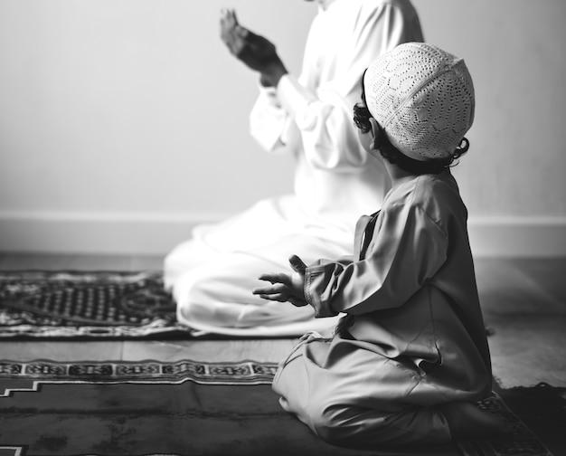Chłopiec muzułmański uczący się, jak robić dua na allaha