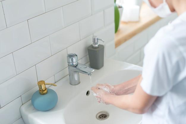 Chłopiec myje jego ręka wysokiego widok