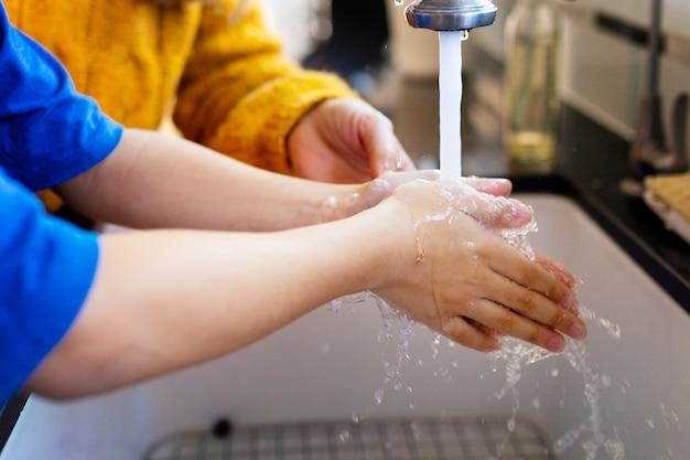 Chłopiec myje ręce, aby zmniejszyć ryzyko covid-19