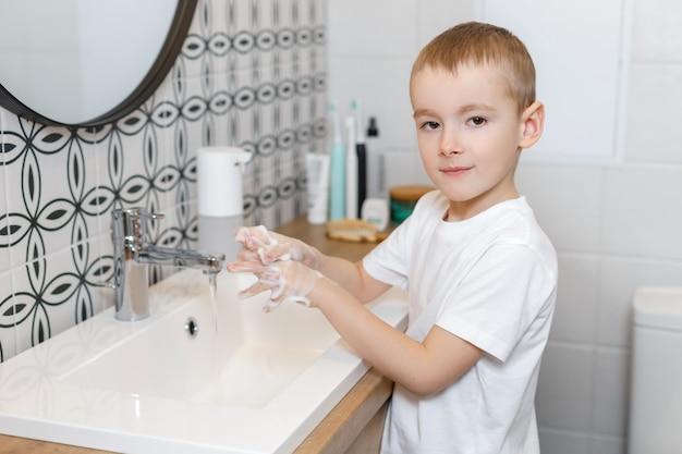 Chłopiec myje ręce w łazience za pomocą dozownika mydła z czujnikiem.