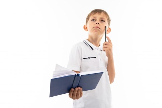 Chłopiec myśli z książką i piórem w ręku na białym