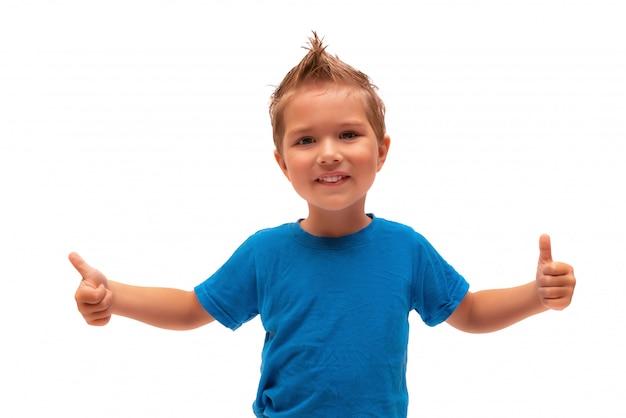 Chłopiec na białym tle uśmiecha się i pokazuje ręce klasy znak