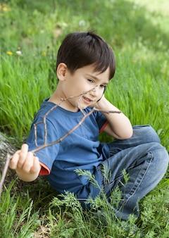Chłopiec na gazonie wśród zielonej trawy