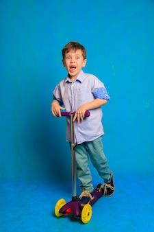 Chłopiec na hulajnodze na niebieskim tle artykuł o hulajnogach dla dzieci a