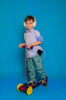 Chłopiec na hulajnodze ze słuchawkami na niebieskim tle artykuł o hulajnogach dla dzieci
