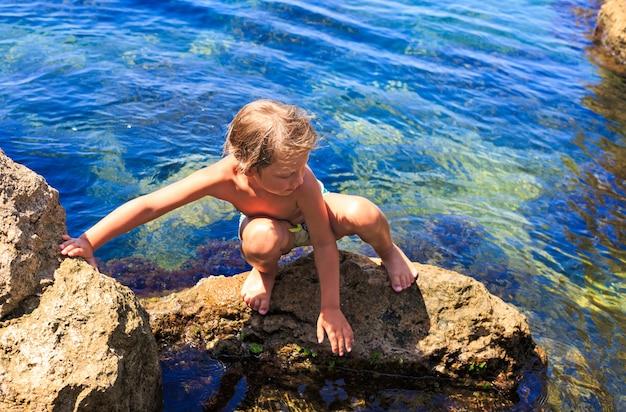 Chłopiec na kamieniach plaży.