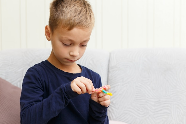Chłopiec na kanapie w domu wyplata bransoletę z gumowych pierścieni