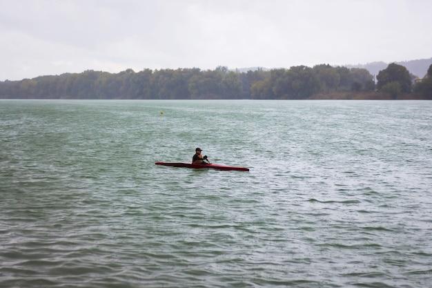 Chłopiec na łodzi sportowej podczas treningu w deszczową pogodę