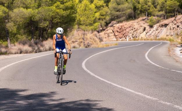 Chłopiec Na Rowerze Na Rowerze Szosowym Na Zewnątrz Na Drodze Z Drzewami W Tle Premium Zdjęcia